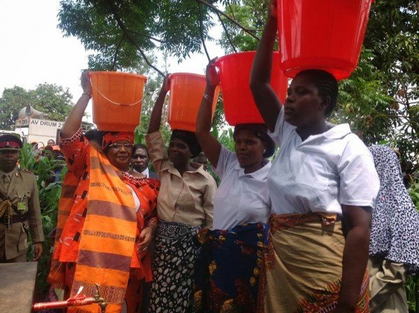 First: Joyce Banda while as President of Malawi carrying a bucket of water