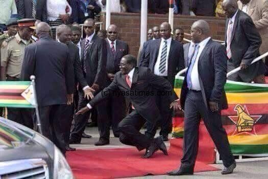 Zimbabwean President Robert Mugabe, center, falls after addressing supporters upon his return from an African Union meeting in Ethiopia. (AP) (The Associated Press)