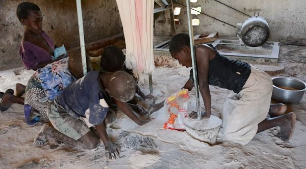 Children scavenge for maize floor at a maize mill in the hunger stricken southern district of Chikwawa. Photo: Thoko Chikondi