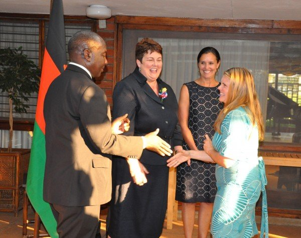 GHS Volunteer being congratulated by PS Msosa as Amb. Palmer and Peace Corps Malawi Director Carol Spahn looks on