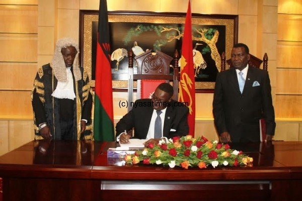 President ProffPeter Mutharika signs the visitors book at Parliament while the Soeaker Richard Msowoya and DPP MP George Chaponda looks on pic by Lisa Vintulla.