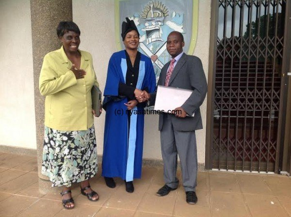 Chirambo(centre) donated laptops to Namalimwe