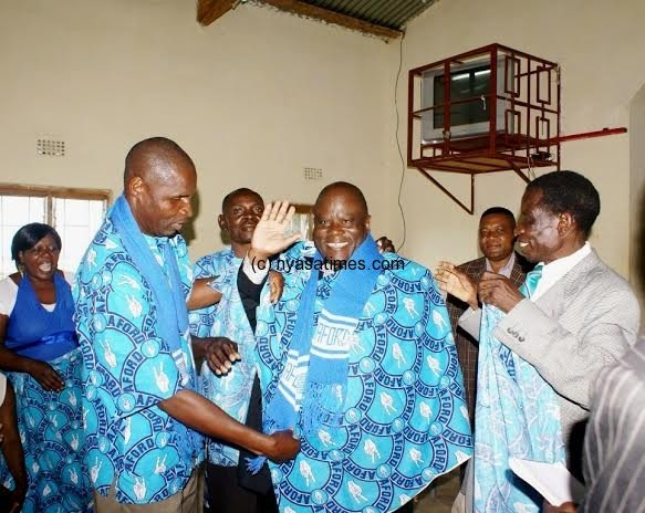 Kakhome- waving- being welcomed to the party by a Mr Kamoto and Makhuwa, AFORD Regional Chairmen for Central and Sourthern Regions respectively- Pic Chancy Gondwe